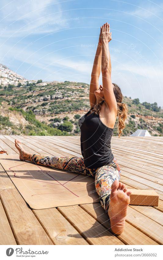 Flexible woman doing stretching exercise during yoga training on sunny day seated wide legged practice camp harmony flexible wellness namaste asana positive