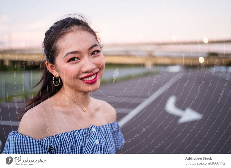 Sincere smiling Asian woman standing on city road in summer sincere accessory smile marking calm sky tranquil satisfied quiet golden earring necklace asphalt