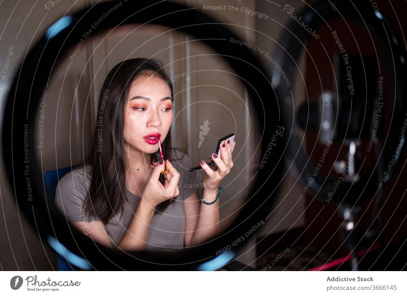 Beauty blogger applying makeup during shooting session beauty vlog woman cosmetic foundation record video young asian female ethnic camera light lamp mirror