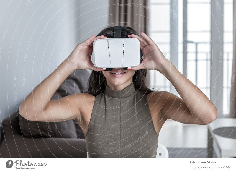 Happy woman using VR goggles while working on laptop vr activity contemporary cyberspace digital headset simulator electronic dimension browsing arm workspace