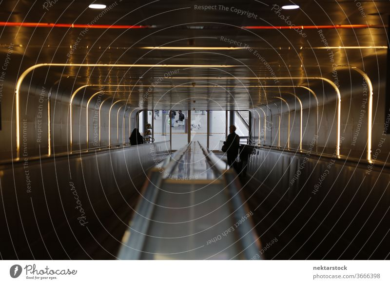Illuminated escalator tube with silhouettes of people day indoors inside interior architecture traveling traveller electricity using power illuminated lit up
