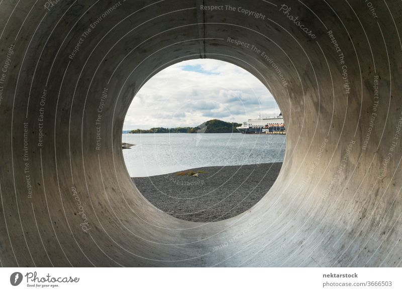 View through concrete pipe to beach and water with cloudscape Oslo Norwegian Norway capital city urban outside outdoors day tunnel view through cylindrical