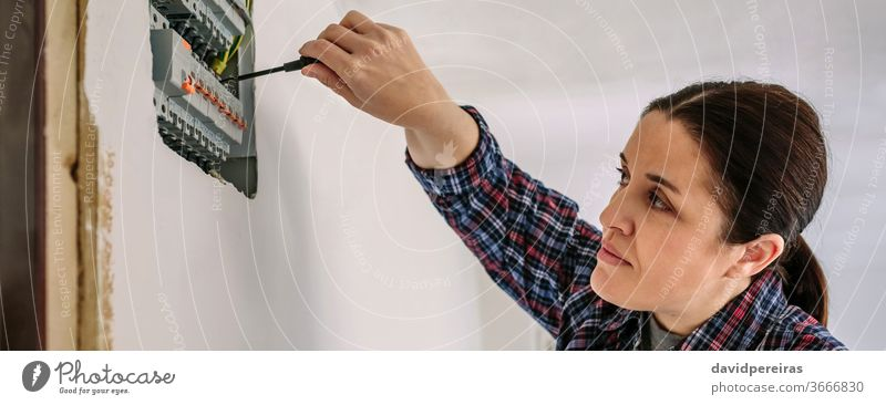 Electrician working on the distribution panel of a house woman electrical technician screwdriver electrician electrical installation inspection testing banner