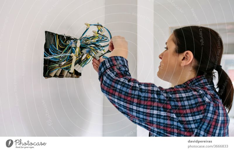 Electrician working on the electrical installation of a house electrical technician female electrician screwdriver connecting electric wire corrugated pipe