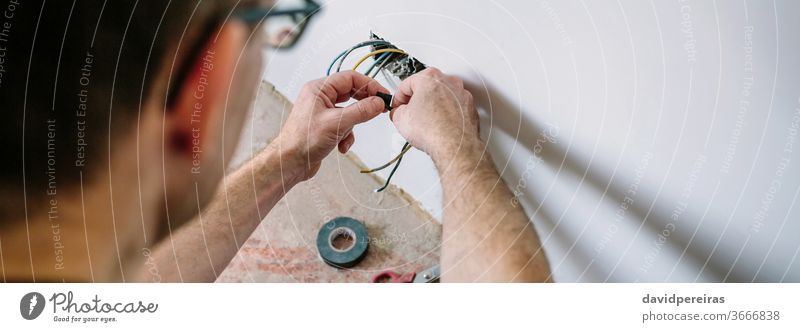 Electrician working on the electrical installation of a house electrician unrecognizable electrical technician connecting wrapping banner web panorama panoramic
