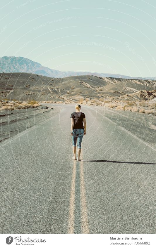 A woman walking barefooted on an empty road in the Death Valley one person caucasian woman death valley the way forward vanishing point freedom landscape travel