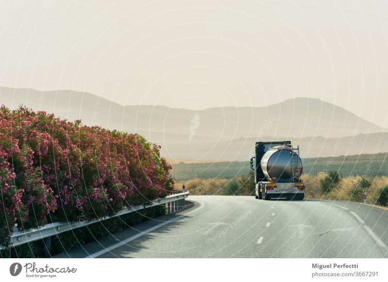 Tanker truck driving on the highway with a background of mountains at sunrise tank truck road travel landscape nature liquid transport mist transportation