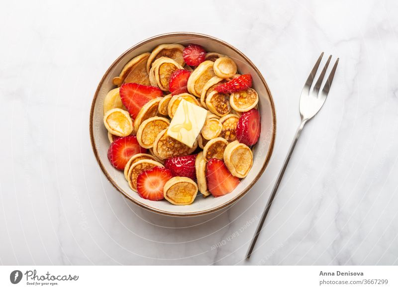 Tiny cereal pancakes and strawberries mini pancakes strawberry breakfast buttter homemade snack tasty sweet food delicious honey syrup tiny trendy food bowl