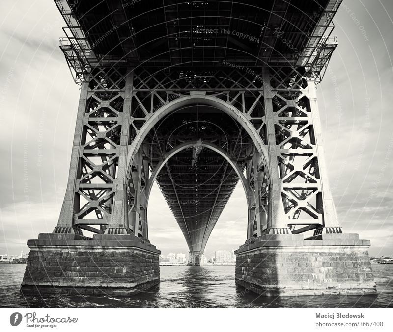 Under the Williamsburg Bridge, New York City, USA. NYC city bridge black and white look up under architecture urban sunset structure view picture river water