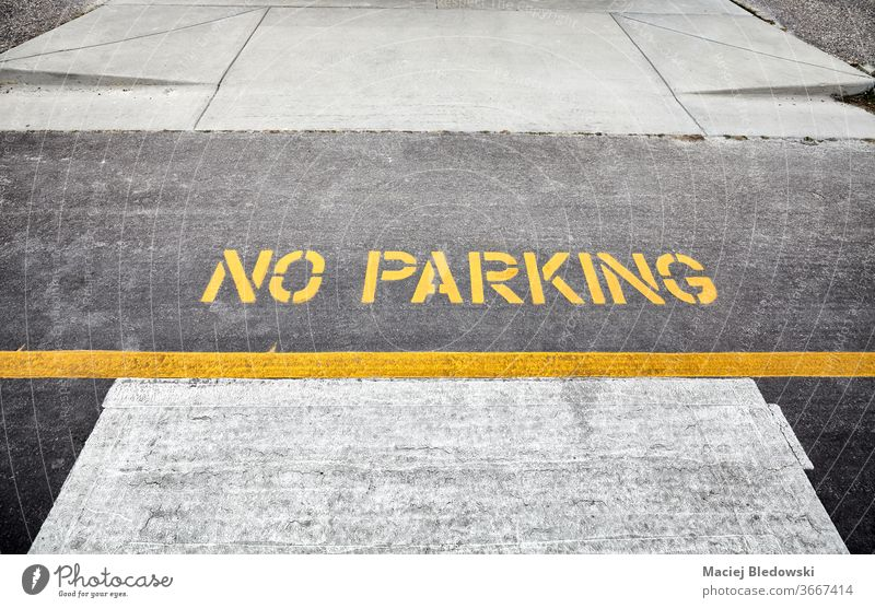 No parking yellow sign painted on a street. no parking symbol road traffic transportation asphalt warning urban line text safety rule restriction no people
