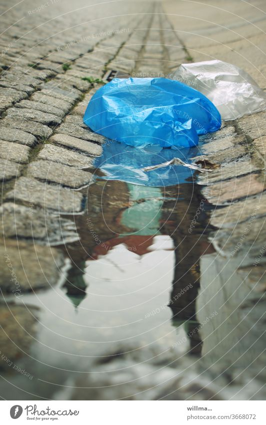 the world sinks into plastic Plastic bag plastic waste Puddle Environmental pollution City hall reflection Paving stone plastic bag Plastic product Marketplace