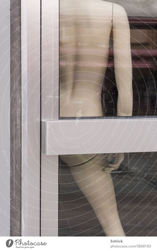 Naked male mannequin behind entrance door made of bright aluminium Detail view Mannequin Front door detail fuselage Manly arm leg by hand Headless shank