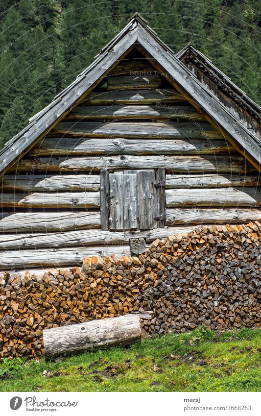 Enough wood in front of the hut with the closed window Firewood stacked Brown Stack of wood Fuel block construction Log cabin Old Weathered natural Idyll