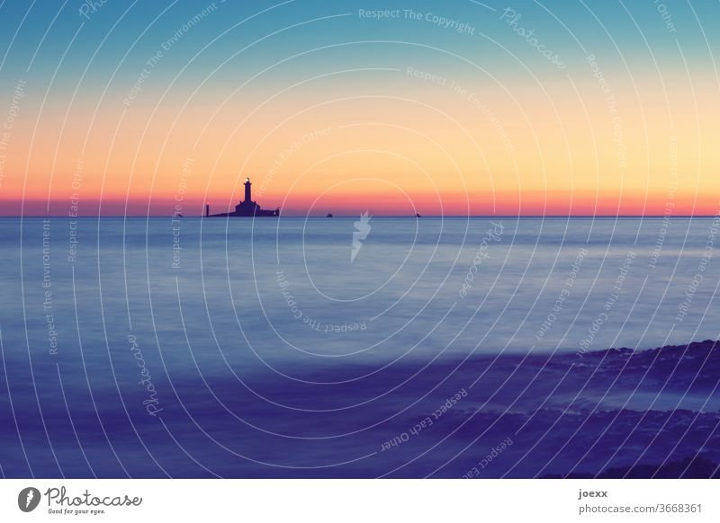 Distant lighthouse on very small island in the sea in sunset mood, long time exposure Lighthouse Historic Horizon Sky Ocean Colour photo Exterior shot Sunset