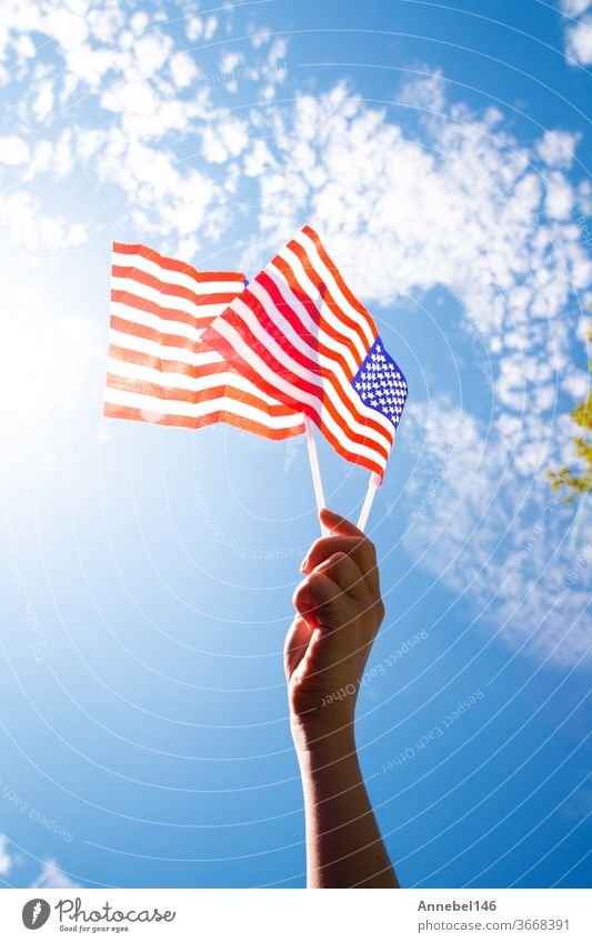 Hand holding two american flags on the blue sky with sunlight background, waving flag for United States of America close-up national patriotism red freedom usa