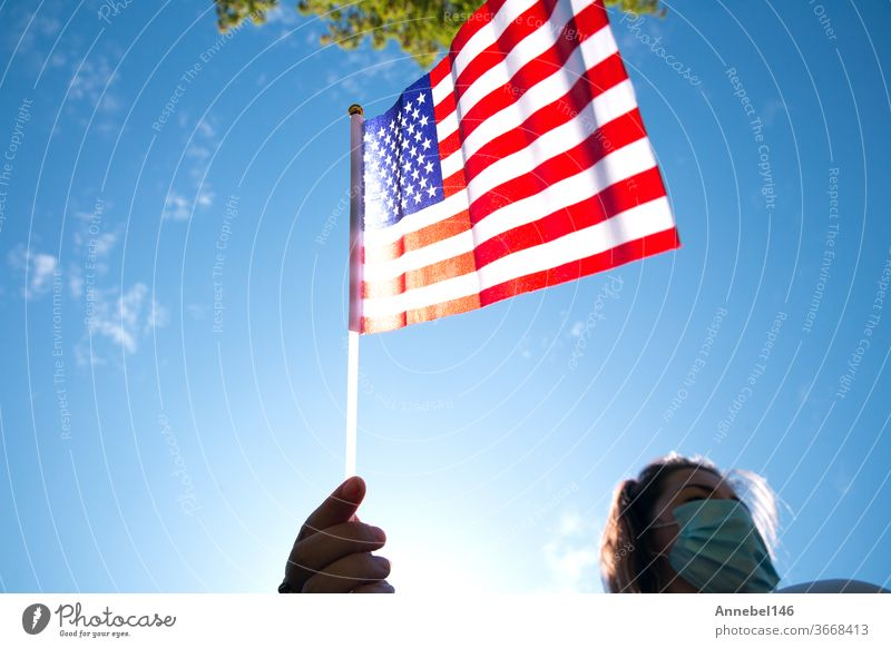 Young woman holding American flag on blue sky with sunlight and safety mask for Covid-19 waving for Usa america usa patriotism outdoors girl freedom patriotic