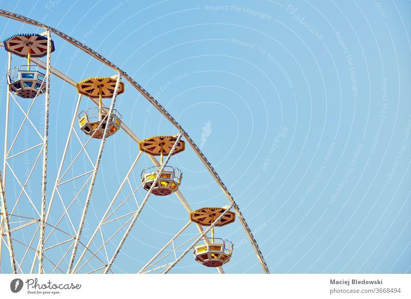 Retro toned picture of a Ferris wheel with cloudless sky. ferris amusement park fun ride childhood retro instagram effect entertainment summer leisure joy