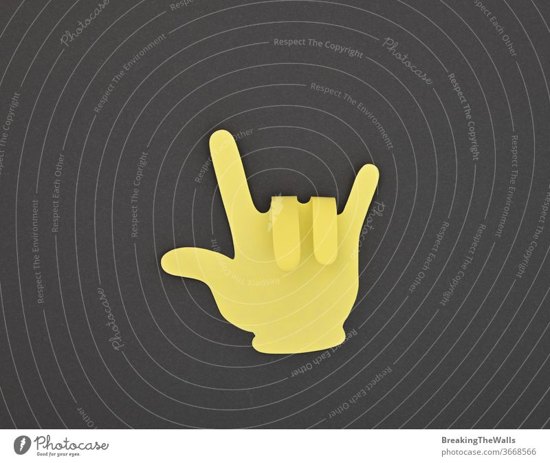 Paper made yellow HORNS gesture sticker on grey Horns devil rock music metal hard heavy good hand shape fingers paper closeup note black background dark
