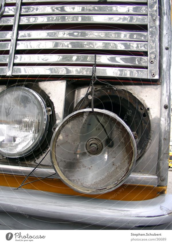 Headlight defective Broken Repaired Scrap metal Wire Transport Floodlight Bus Close-up Front side