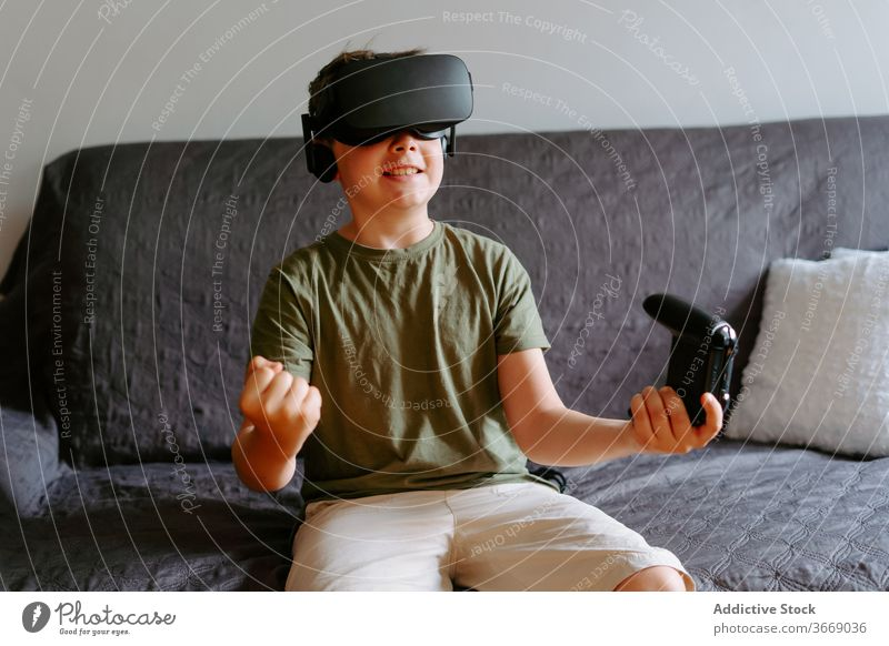 Child in VR headset playing on couch boy vr goggles gamepad virtual reality using sofa entertain modern home device child kid little adorable gadget childhood