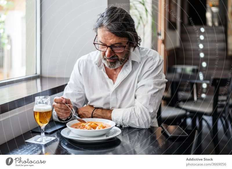 Bearded ethnic man eating delicious lunch in restaurant elderly cafe glass beer mature drink positive male smile aged retire bar chill meal eyeglasses beverage