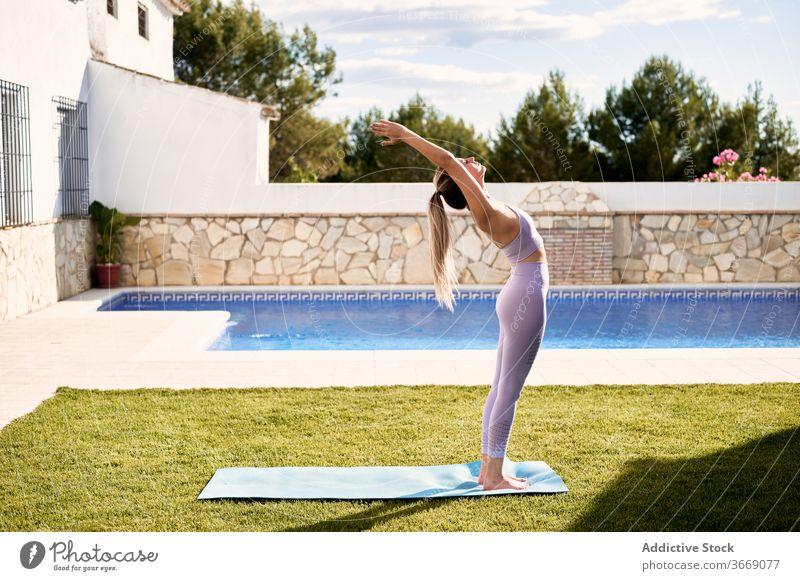 Calm woman doing yoga in Mountain position on terrace mountain pose urdhva hastasana practice summer mat stress relief female slim bra leggings pool calm