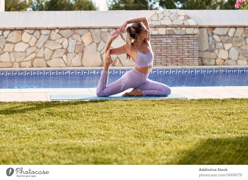 Flexible woman doing yoga in King Pigeon pose king pigeon pose practice eka pada rajakapotasana courtyard mat tranquil flexible harmony female active wear