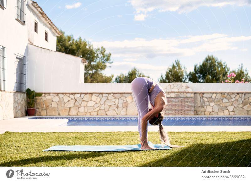 Woman doing yoga in Uttanasana on terrace forward bend practice woman uttanasana flexible pose lawn female sportswear mat healthy exercise stretch wellness