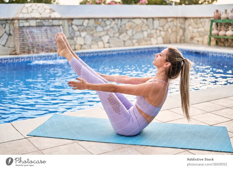 Woman in Boat pose on yoga mat boat pose practice woman balance active wear poolside summer flexible concentrate female wellness body asana courtyard relax
