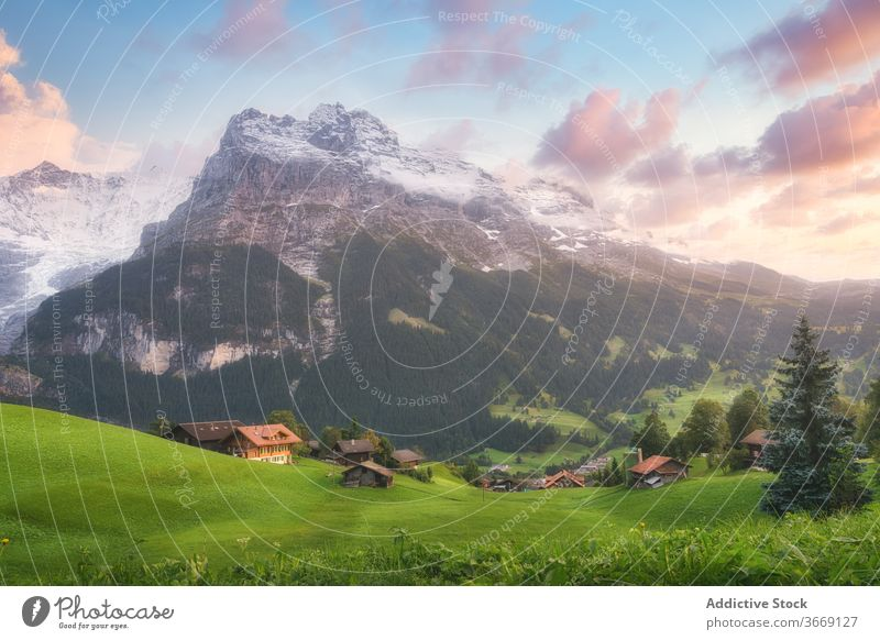 Green hill with houses near rough mountains under cloudy sky village ridge picturesque idyllic highland blue sky colorful harmony snowy majestic breathtaking