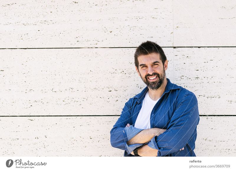 Bearded man leaning on wall with crossed arms while looking camera with a smile 1 male standing bearded cheerful attractive hispanic arms crossed casual attire