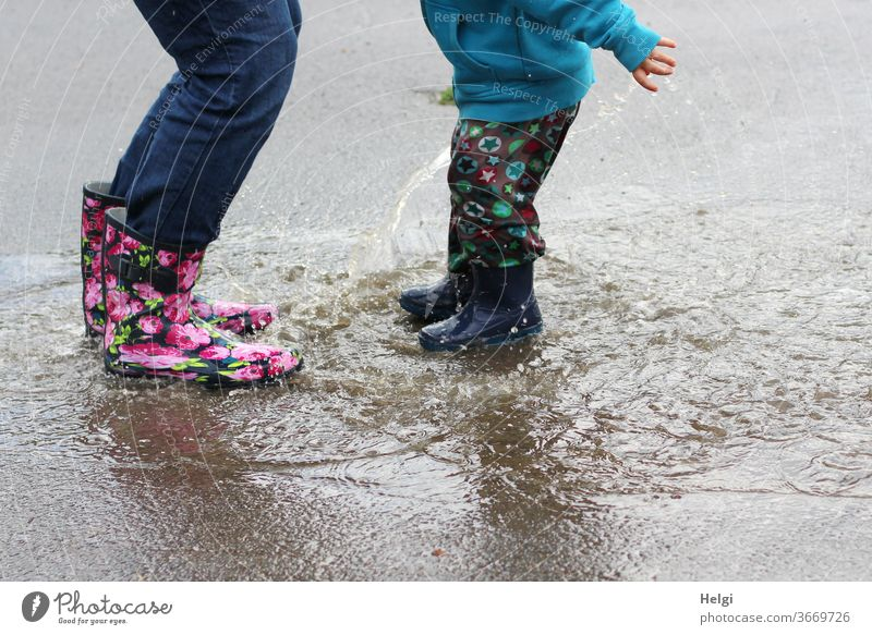 Puddle fun - mother and child have fun jumping into the puddle Mother Child Detail Legs Rubber boots Jump splat Joy Splash Inject Water Wet Rain Playing