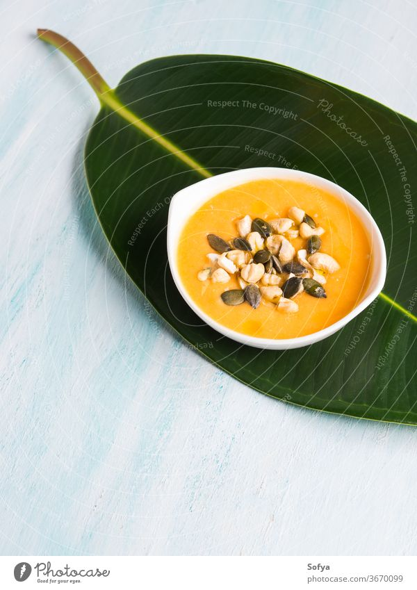 Pumpkin creamy soup served on green leaf pumpkin bowl food healthy meal vegetable bean white cannellini italian dinner yellow cuisine rustic lunch vegetarian