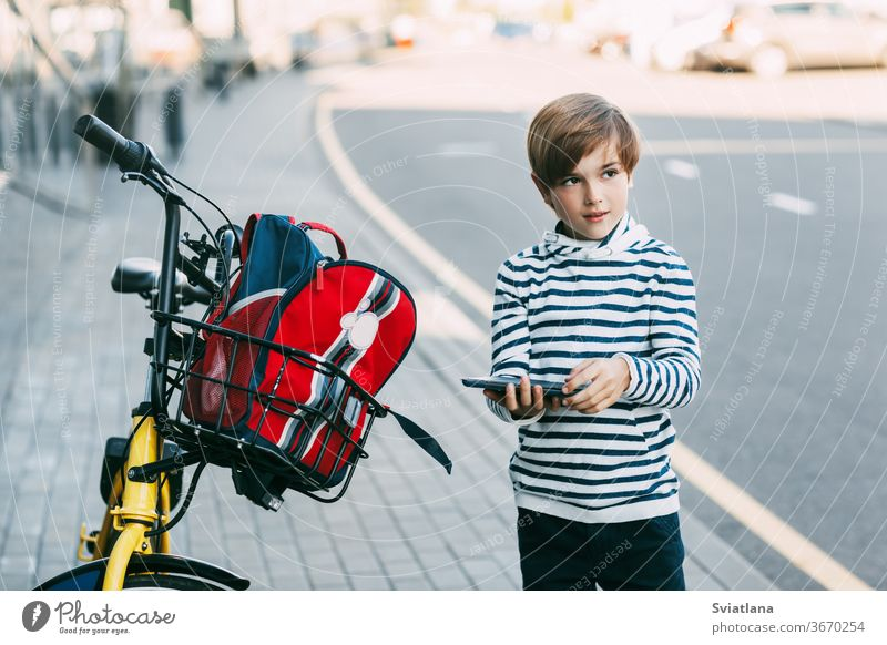 A cute boy in a striped sweater holds a tablet in his hands and stands next to a Bicycle with a backpack hanging from it. The boy is going to ride home after school on a Bicycle. Safe way home