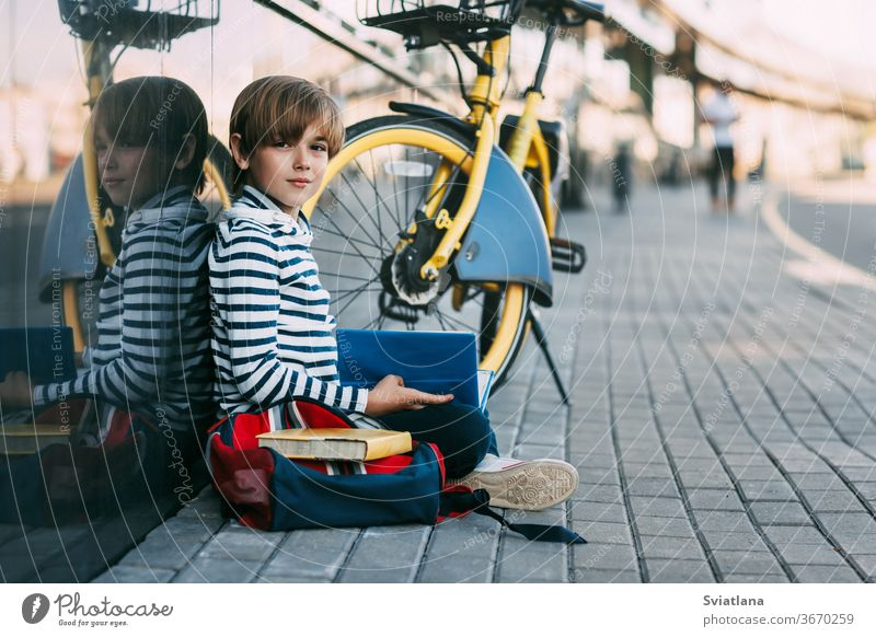 A cute schoolboy is sitting in the open air at school and holding a book in his hands. Next to it is a school backpack and a Bicycle, space for text face tired