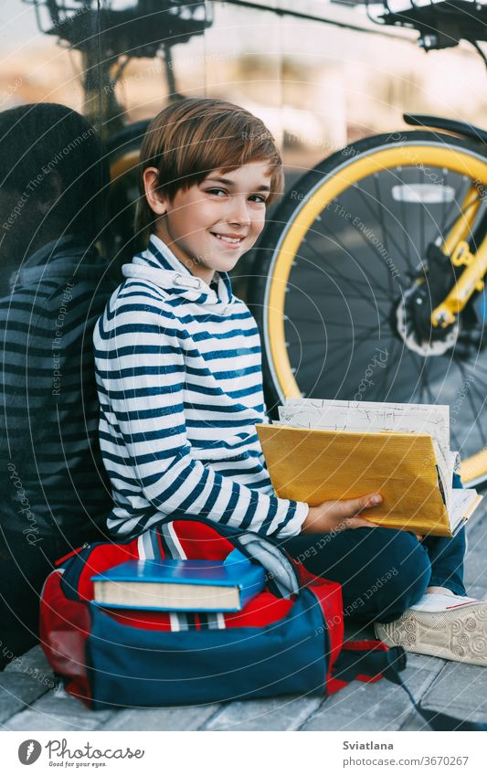 A cheerful boy is sitting on the sidewalk near the school and reading a book. Next to it is a Bicycle and a backpack face tired cover education portrait holding