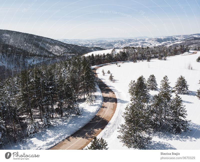 Winter landscape in sunlight. View on the mountain road surrounded by evergreen trees in winter, drone shot above aerial asphalt background cabin cold