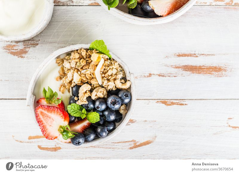 Bowl of natural yogurt with granola and fresh berries breakfast healthy muesli food fruit meal white dessert sweet bowl organic greek wooden cereal glass snack