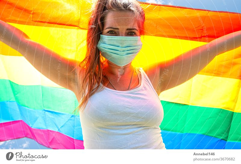Young woman waving a rainbow flag for LGBT rights, freedom for homosexual Lgbtq concept, wearing a safety mask for Covid-19, coronavirus. Protesting lesbian