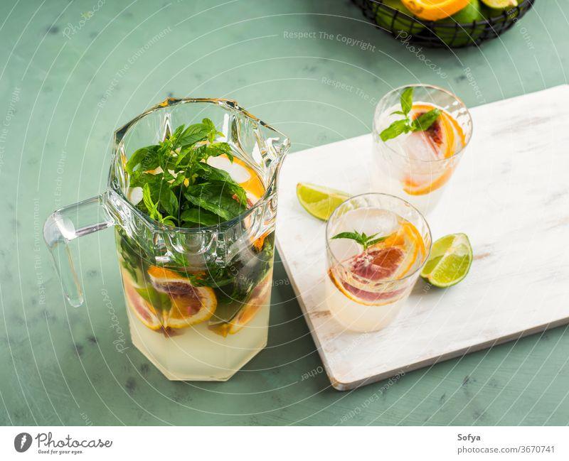 Fresh summer citrus drink with ice on green water cocktail lemonade infused detox mocktail blood orange lime fruit juice mint soda sweet home made slice healthy