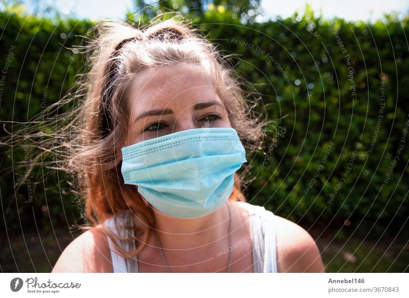 Young woman wearing facemask, safety mask for COVID-19, Coronavirus. Portrait of adult girl outside. Concept for flu or coronavirus infection young epidemic