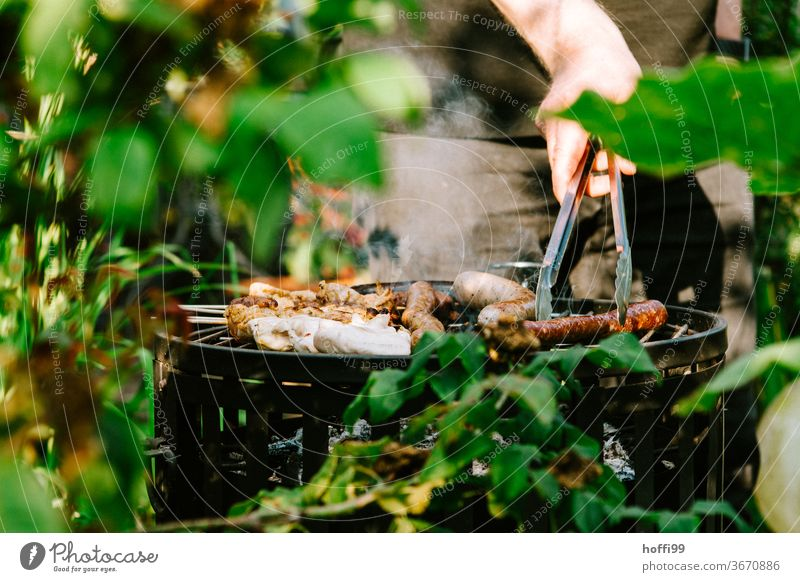 Please turn - the sausage on the grill is turned BBQ by hand barbecue tongs charcoal grill Small sausage barbecue food grilled meat Barbecue (apparatus)