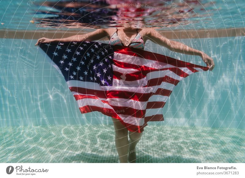 young woman in a pool holding american flag underwater. 4th july independence day concept. Summertime swimming pool summer sunglasses caucasian fun beautiful