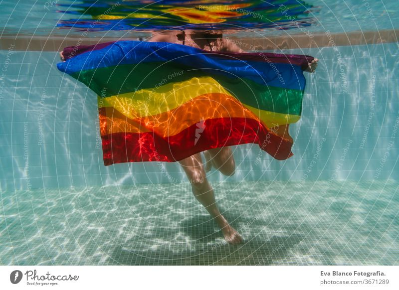 young woman in a pool holding rainbow gay flag underwater.LGBTQ concept. Summertime swimming pool love hugs lesbian homosexual equality attractive people female