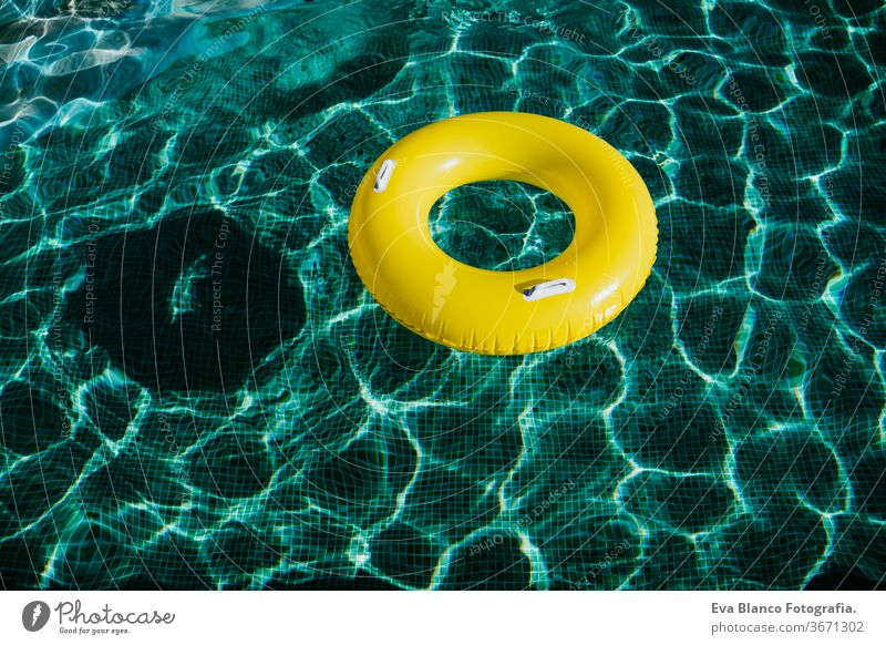 yellow inflatable donuts floating in a swimming pool. Nobody. Summer time concept nobody summer blue water toy ring preserver emergency colors circle abstract