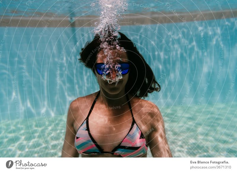 young woman diving underwater in a pool. summer and fun lifestyle sunglasses swimming bubbles caucasian dive clear health light action wet swimmer blue active