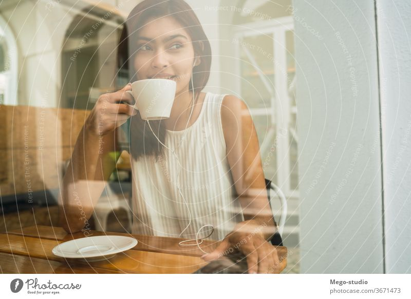 Young woman drinking a cup of coffee at coffee shop. young portrait latin outdoors cafe brunette time off confident leisure free time lifestyle refreshment