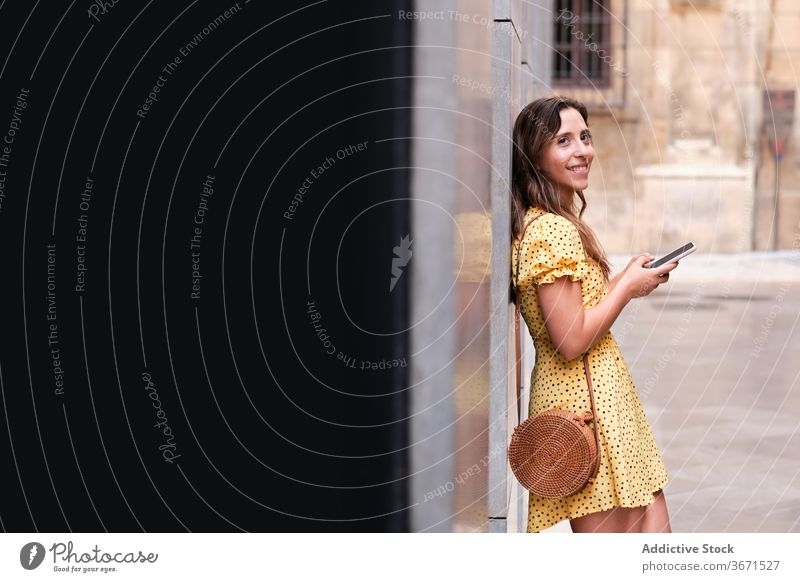 Cheerful woman using smartphone in city stroll summer building urban smile browsing female dress cheerful mobile phone online lean surfing device gadget lady
