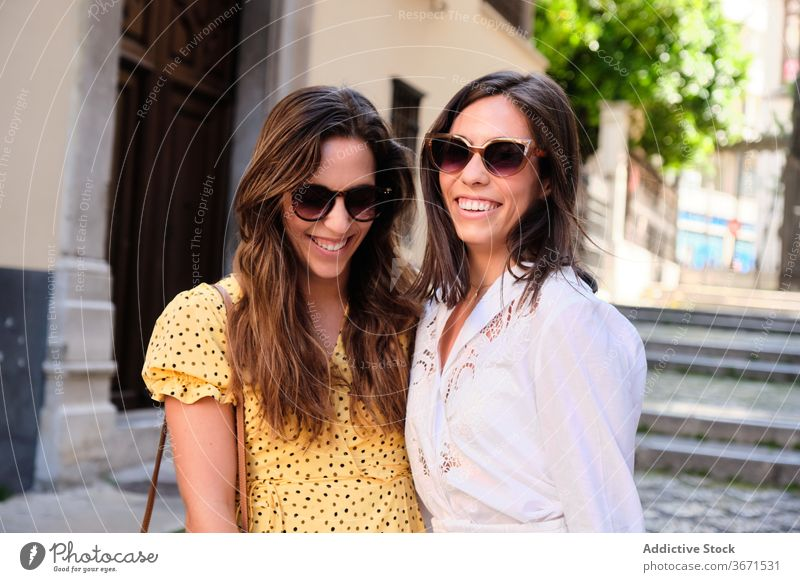 Delighted female friends walking along street women city friendship enjoy weekend hug together delight stroll summer young smile cheerful happy carefree