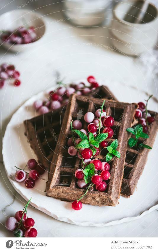 Oatmeal chocolate waffles with gooseberries oatmeal kitchen culinary vertical timber homemade bake food pastry table detail food composition natural dish style